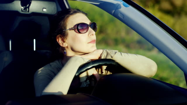 A woman in sunglasses relaxes in the car. Sits behind the wheel, admiring the beautiful scenery at sunset. Happy driver of the concept video