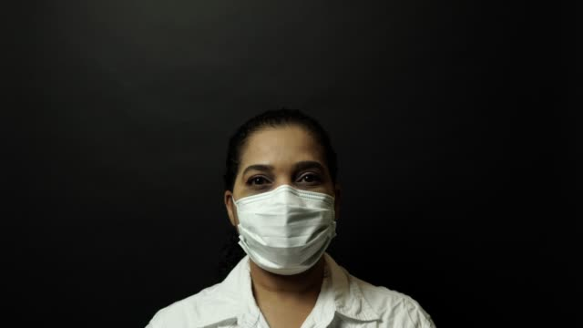 Woman in surgical or medical mask with open eyes, looking at the camera on black background. Coronavirus pathogen outbreak concept. Bacterium and virus disease 2019-nCoV protection and prevention. 4k.