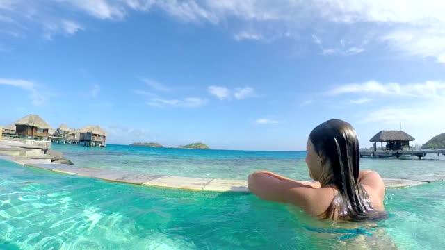 Woman in swimming pool enjoying the view at luxury resort video