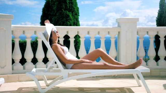 Woman in swimsuit lying on deck chair enjoying sunbathing having good time outdoor