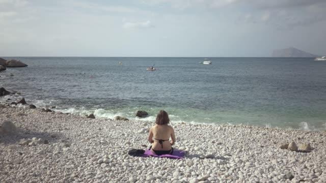 kvinna i baddräkt sitter på en strandhandduk och njuter av solen - människorygg bildbanksvideor och videomaterial från bakom kulisserna