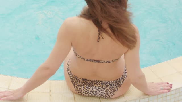 Woman in swimsuit sitting on the edge of small swimming pool in courtyard video