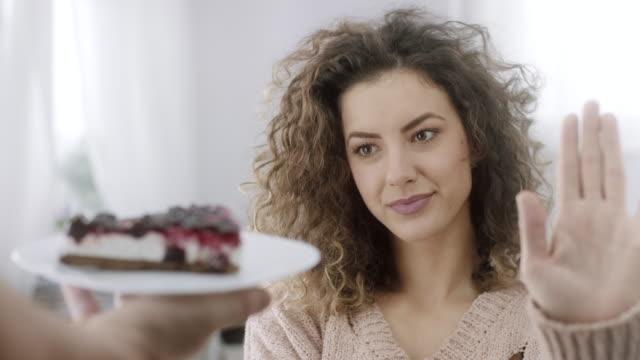 vidéos et rushes de femme dans la tentation refusant la tranche de gâteau - tentation