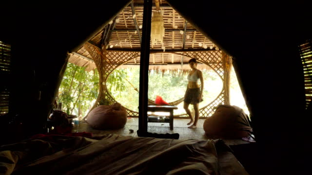 Woman in Tent interior in a tropical forest in El Nido, Philippines