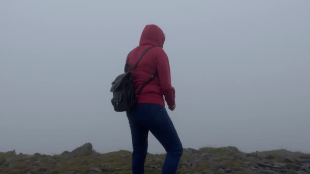 Woman in the cold cloud on top of mount video