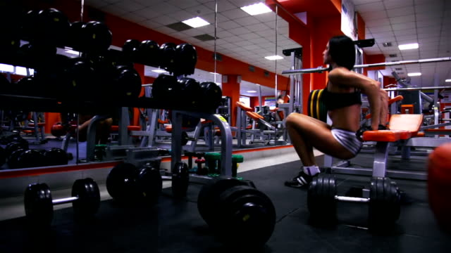 Woman in the gym does reverse squats video