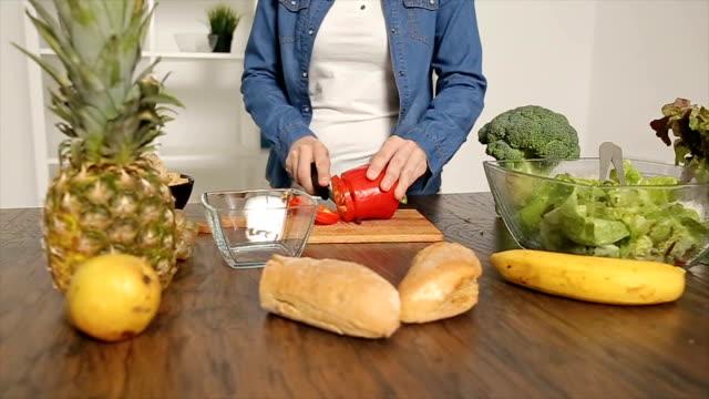女性のキッチンでカティングピーマン ビデオ
