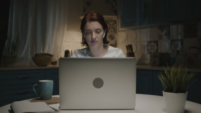 vidéos et rushes de femme dans la cuisine avec l'ordinateur portatif. - boisson chaude