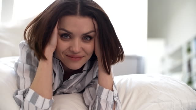 Woman in the Morning Portrait of young Caucasian woman in stripped shirt lying in bed under blanket, looking at camera, touching her head and hair with her hands and smiling hairstyle stock videos & royalty-free footage