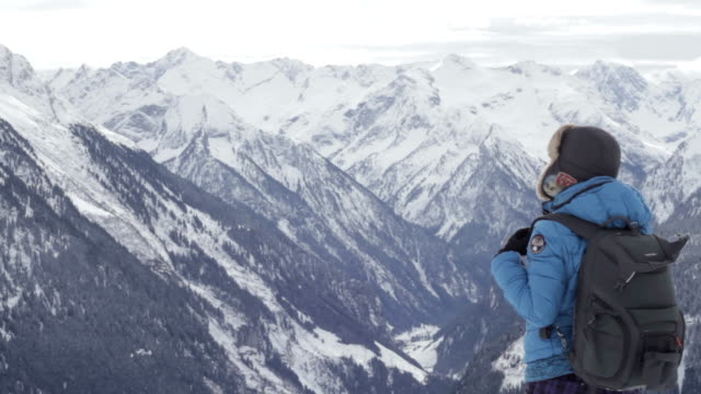 Woman in the mountains looking at beautiful view, video