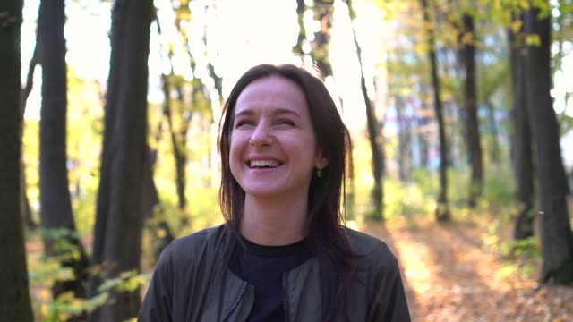 Woman in the park. True positive emotions. Charming young woman with long hair smiles. Steady shot. Slow motion