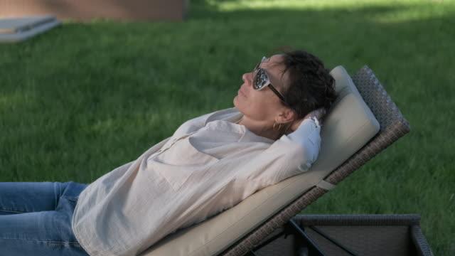 a woman in the resort is in a lounge chair. - wschodnio europejski filmów i materiałów b-roll