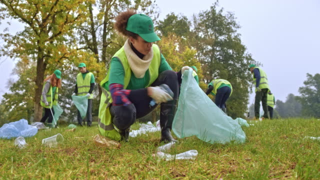 Woman in the volunteer cleaning crew picking up litter and placing it into the garbage bag