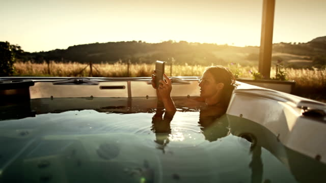 Woman in thermal bath with digital tablet video