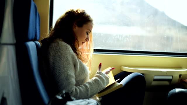 vídeos y material grabado en eventos de stock de mujer en el tren leyendo libro - tren
