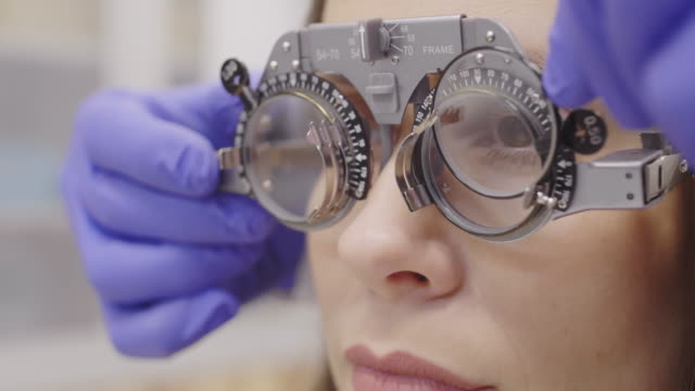 Woman in Trial Frame with Lenses Covering One Eye and Speaking with Optometrist Close up view of woman in trial frame looking in front of her while optometrist inserting lens, then covering one eye and telling something during vision test in clinic ophthalmologist stock videos & royalty-free footage