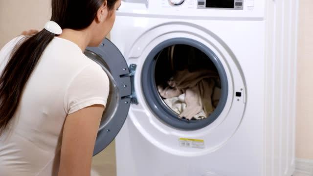 frau im t-shirt nimmt saubere wäsche der waschmaschine - waschmaschine wand stock-videos und b-roll-filmmaterial