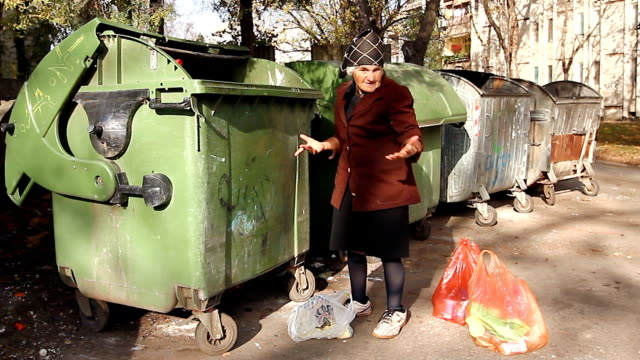 Woman in urban poverty Homeless woman is searching for food in garbage dumpster. Woman in poverty is searching something in container. scavenging stock videos & royalty-free footage