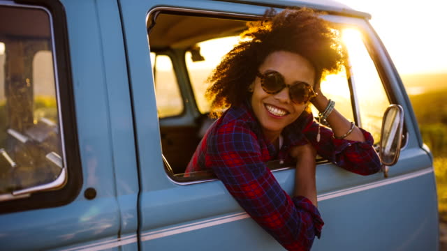 Woman in vintage car laughing at sunset