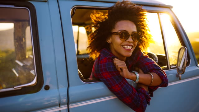 Woman in vintage car laughing at sunset video