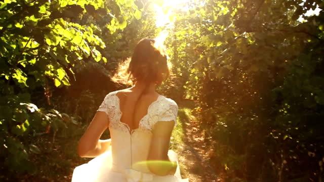 女性は、ビンテージのウェディングドレスのランニングスローモーションの森 - 春のファッション点の映像素材/bロール