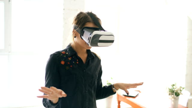 Woman in VR headset looking up and trying to touch objects in virtual reality at home indoors video