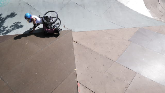 vídeos y material grabado en eventos de stock de mujer en silla de ruedas en el parque de patinaje - de pie después de caerse - deportes en silla de ruedas