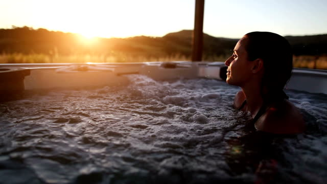 Woman in whirlpool hot tub Woman in whirlpool hot tub at sunset spa treatment stock videos & royalty-free footage