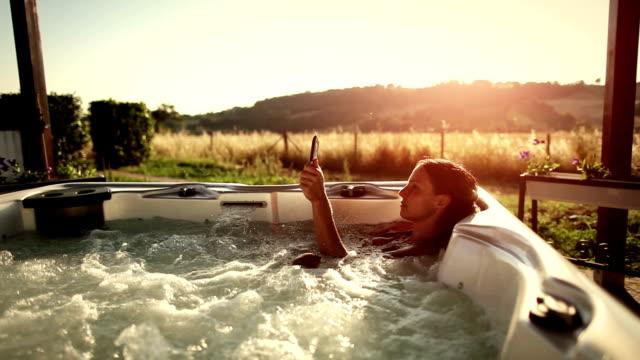stockvideo's en b-roll-footage met woman in whirlpool hot tub with digital tablet - spa behandeling