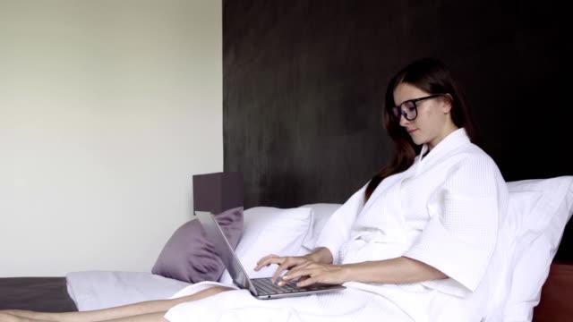 vidéos et rushes de femme en peignoir blanc et verres travaillant sur ordinateur portable, assis sur le lit. sourire féminin et travail sur ordinateur. affaires en ligne. - peignoir
