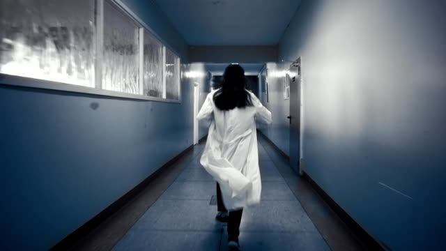 Woman in white coat running down a dark corridor, view from back. video
