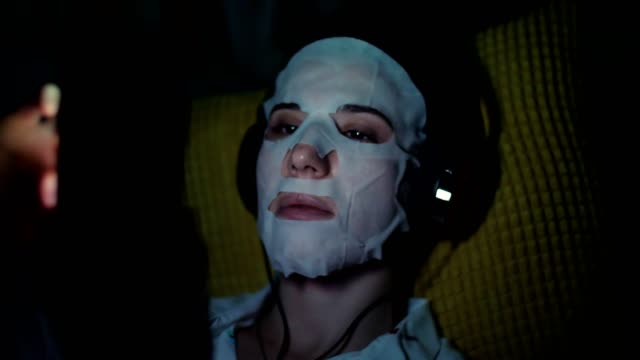 woman in white cosmetic fabric mask, with headphones, holds smartphone, mobile in hands. listening, watching smth, at night, lying on sofa, in front of screen - vídeo