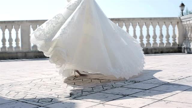 vídeos de stock, filmes e b-roll de mulher no vestido branco que gira ao ar livre nenhum ângulo baixo do movimento lento da cara. noiva em laço vestido de dança girando ao redor no terraço varanda piso segurando bordados hem comemorando casamento casamento desfile de moda - saia