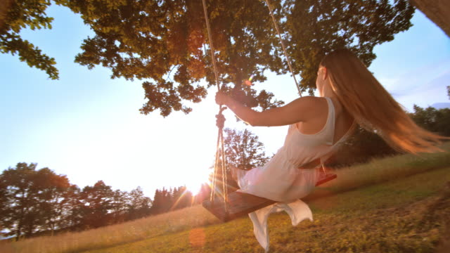 SLO MO Woman in white dress swinging at sunset Slow motion medium tracking shot of a woman with long hair in a white dress swinging under a big tree into the setting sun. swinging stock videos & royalty-free footage