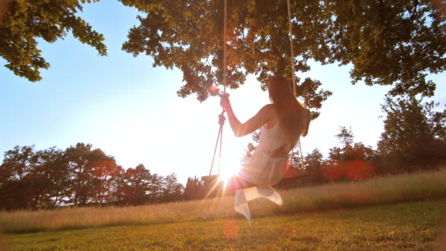 SLO MO Woman in white dress swinging towards the sun video
