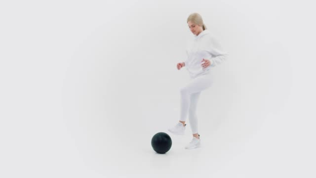 Frau im weißen Sportkleid mit schwarzem Ball – Video