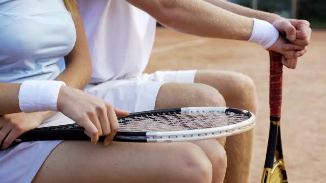 stockvideo's en b-roll-footage met vrouw in wit sport kleding zittend op een bankje en flirten met trainer, sport - kampioenschap