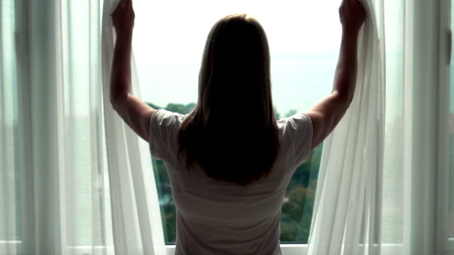 Woman in white t-shirt unveiling curtains and looking out of window. Enjoying the sea view outside video
