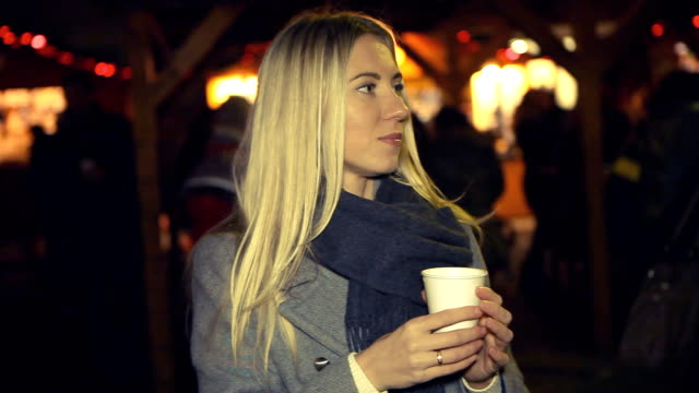 Woman in white with cup of coffee at the winter weather, Christmas Fair