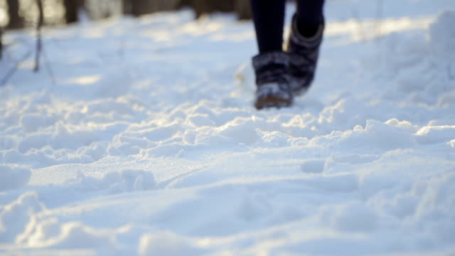 woman in winter boots walk on snow in slow motion - fare un passo video stock e b–roll