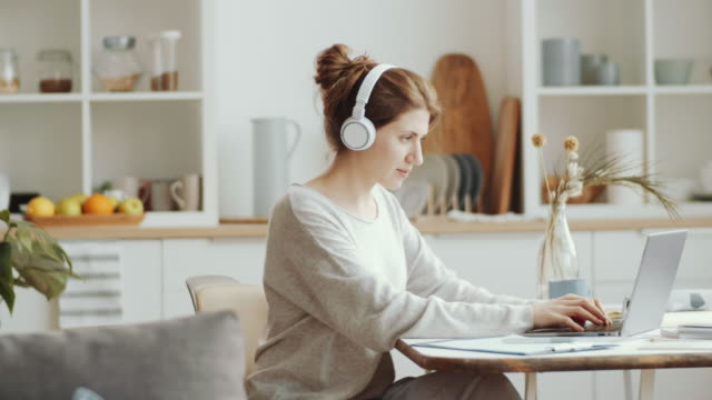 vídeos de stock e filmes b-roll de woman in wireless headphones working on laptop at home - remote work