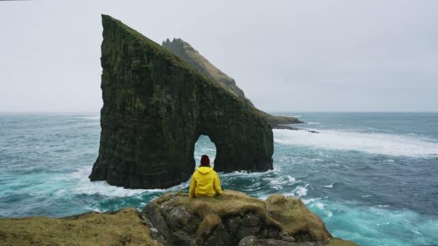 kvinna i gul regnrock tittar på drangarnir båge i färöarna - vidbild bildbanksvideor och videomaterial från bakom kulisserna