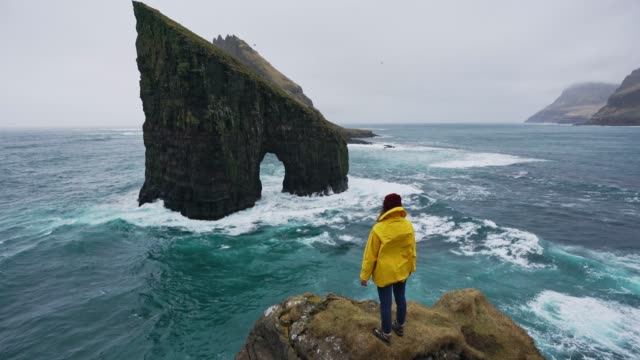 woman in yellow raincoat looking at drangarnir arch in faroe islands - cliffs stock videos & royalty-free footage