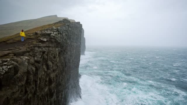 Woman in yellow raincoat  looking at scenic  view of seaside in Faroe Islands