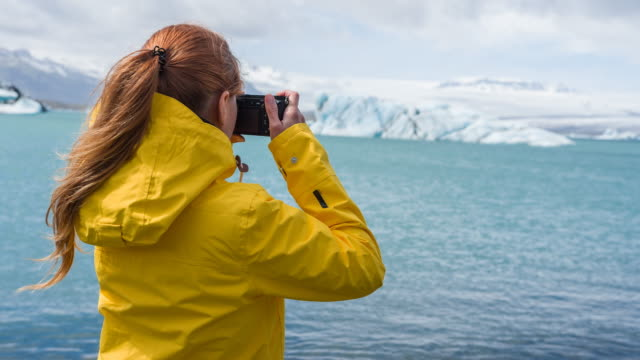 Woman in yellow raincoat photographing icebergs floating in water video