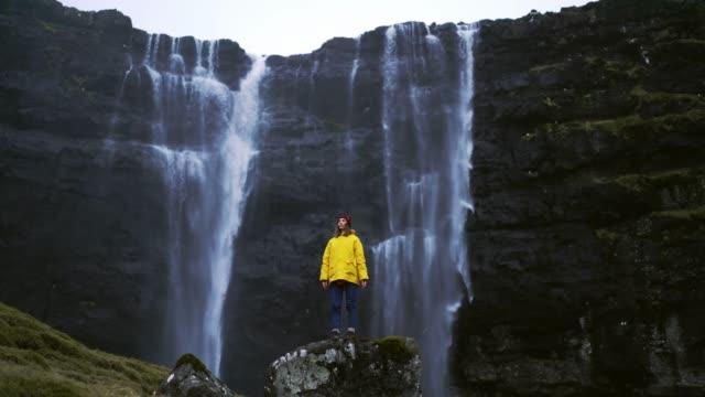 vídeos de stock, filmes e b-roll de mulher no capa amarelo que está perto da cachoeira em consoles de faroe - contrastes