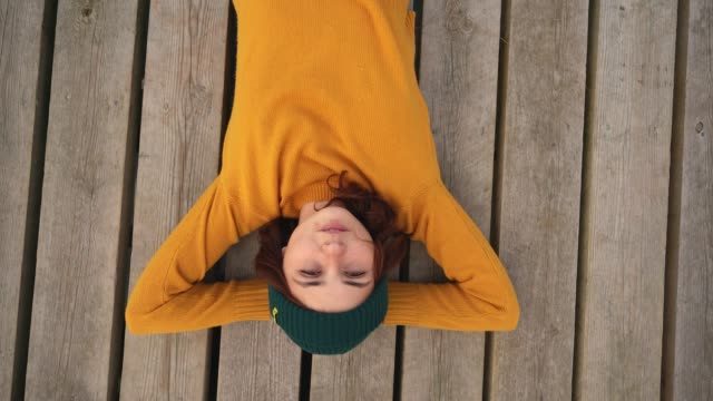 Woman in yellow sweater laying on pier and looking up