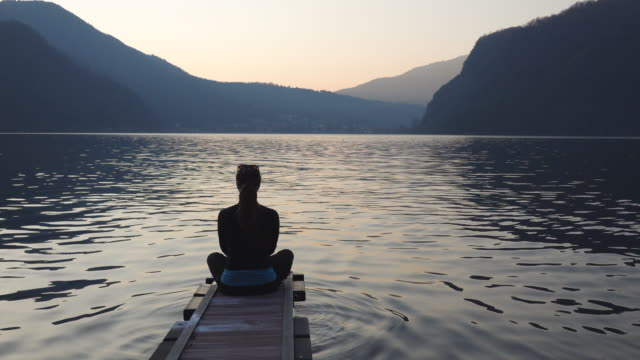 Woman in yoga pose at the end of dock on lake meditating