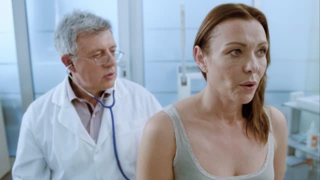 donna inspirando ed espirando, è il suo medico auscultating polmoni - stetoscopio video stock e b–roll