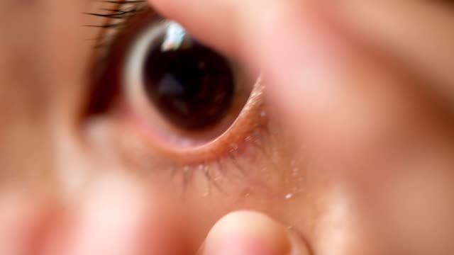 vídeos de stock e filmes b-roll de mulher inserir lente de contacto - contacts